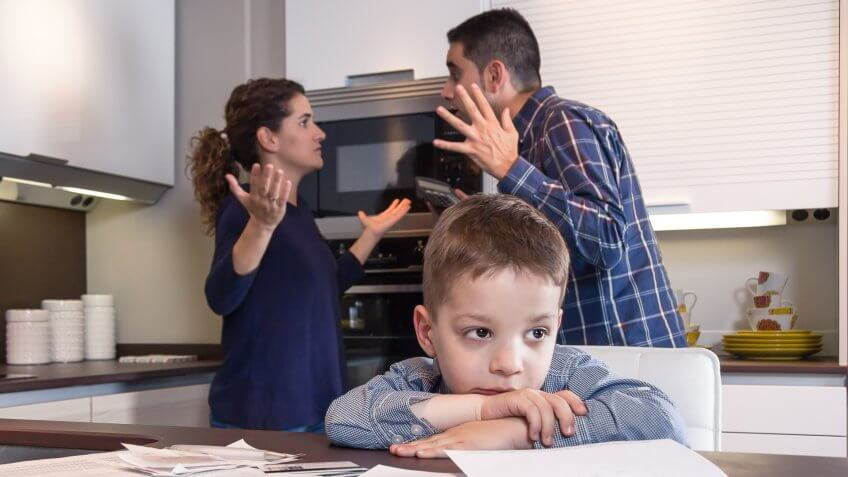 Sad child suffering and his parents having hard discussion in a home kitchen by couple difficulties.