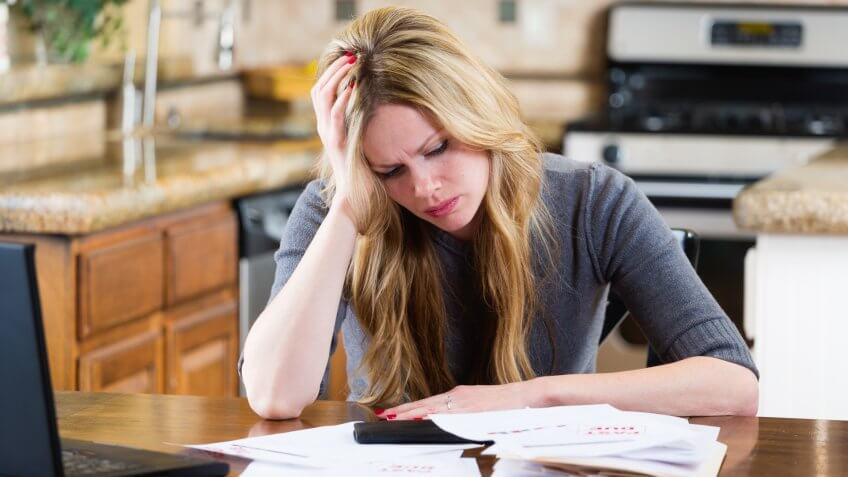 A woman overwhelmed with past-due bills and debt.