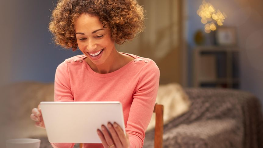 a young woman sits at home at night , going through her domestic bills  and comparing them with comparison websites using her digital tablet , or internet shopping.