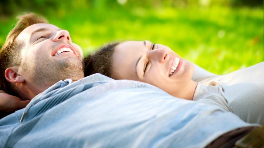 Happy Smiling Couple Relaxing on Green Grass.