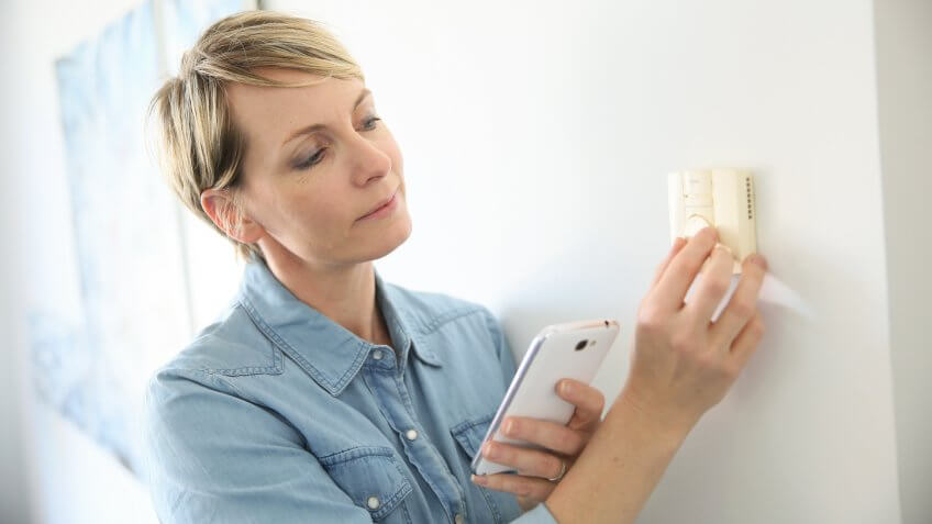Woman porgramming indoor temperature with smartphone application.