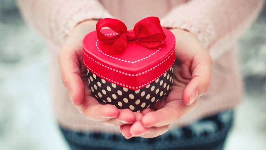 Female hands holding a gift box shaped of heart.