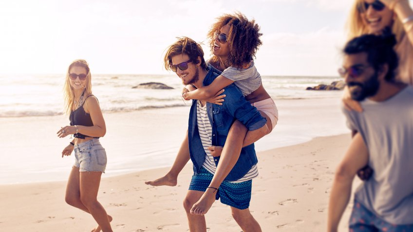 Two happy young men giving their girlfriends piggyback rides at the beach.