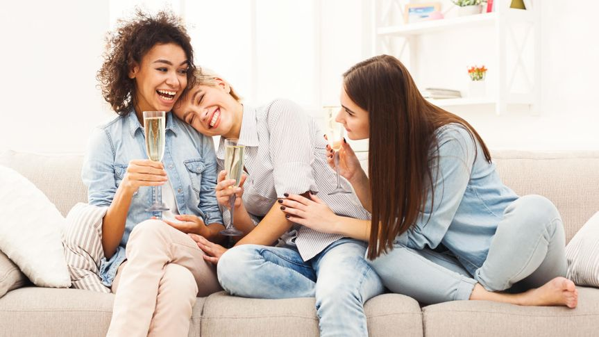 Happy female friends chatting and drinking wine at home.