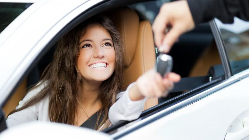 Young woman receiving the keys of her new car.