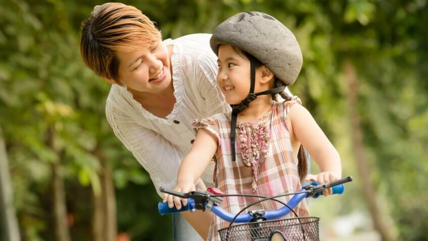 Vintage of little Asian child with mother practice to riding a bicycle.