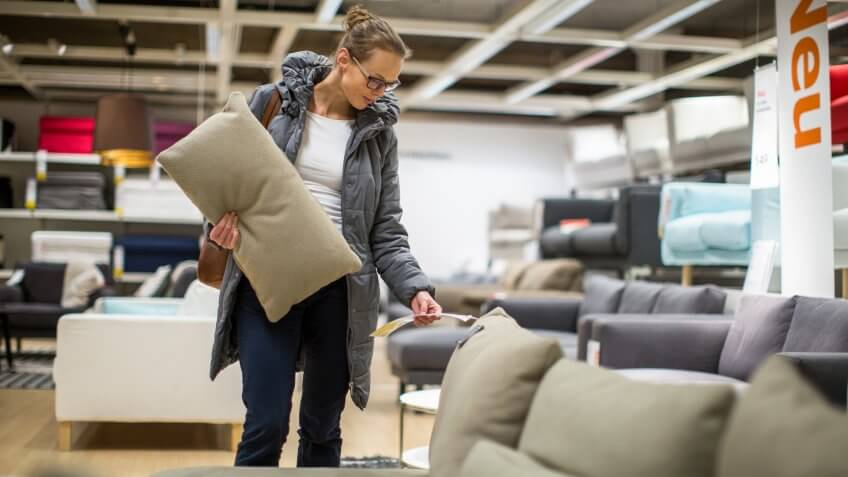 Pretty, young woman choosing the right furniture for her apartment in a modern home furnishings store