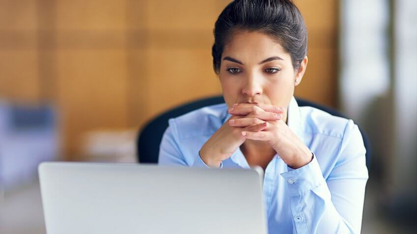 Shot of a young businesswoman looking stressed while working at her desk