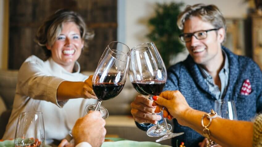 People cheering at celebration table with wine glasses and smiles on their faces.