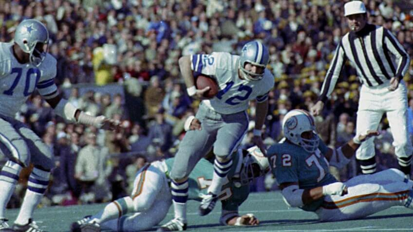 Roger Staubach; Jim Riley Dallas Cowboys quarterback Roger Staubach (12) tries to escape the grasp of Miami Dolphins defender Jim Riley (70) during action of Super Bowl VI in New Orleans, La.