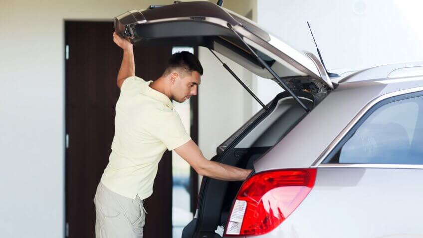 road trip, transport, private property leisure and people concept - young man with open car trunk at parking space.