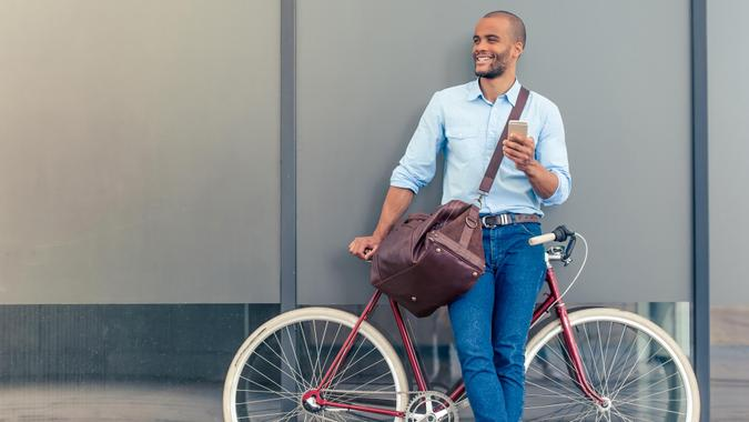 Full length portrait of handsome young Afro American man in casual clothes using phone, looking away and smiling while leaning on his bike, standing outdoors.
