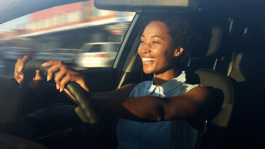 Portrait of smiling young african american woman driving a car.