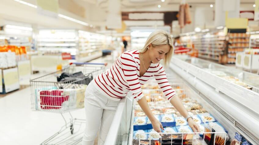 woman buying refrigerated food in a grocery supermarket