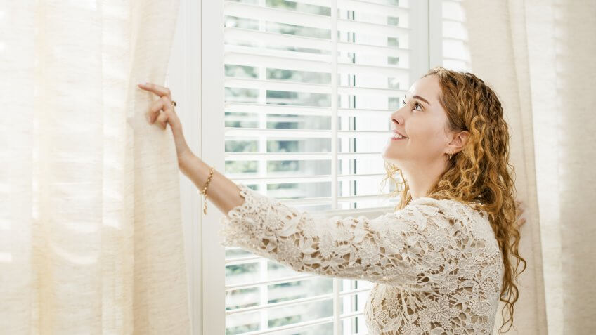 person opening Drapes and Blinds