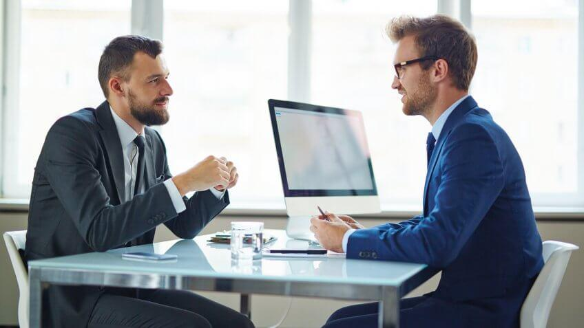 Two men speaking to each other at a table at work