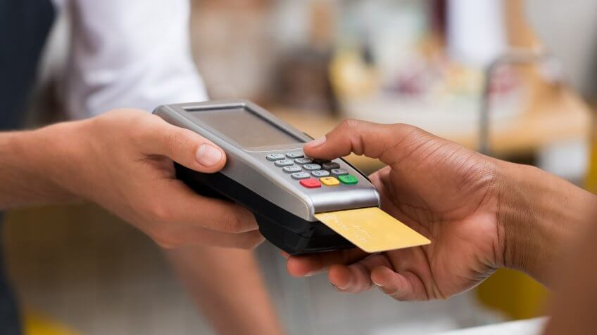 Close up of person paying with their credit card