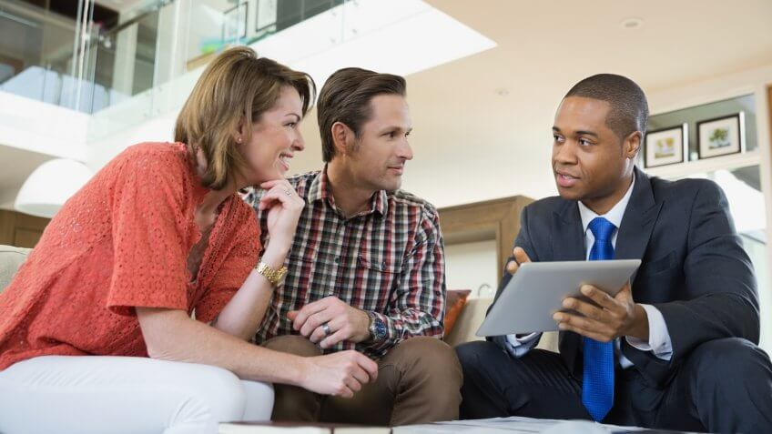 Couple talking to financial advisor in living room.
