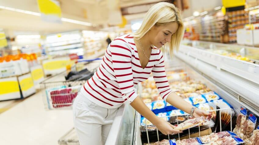 Woman shopping for refrigerated food at the grocery supermarket