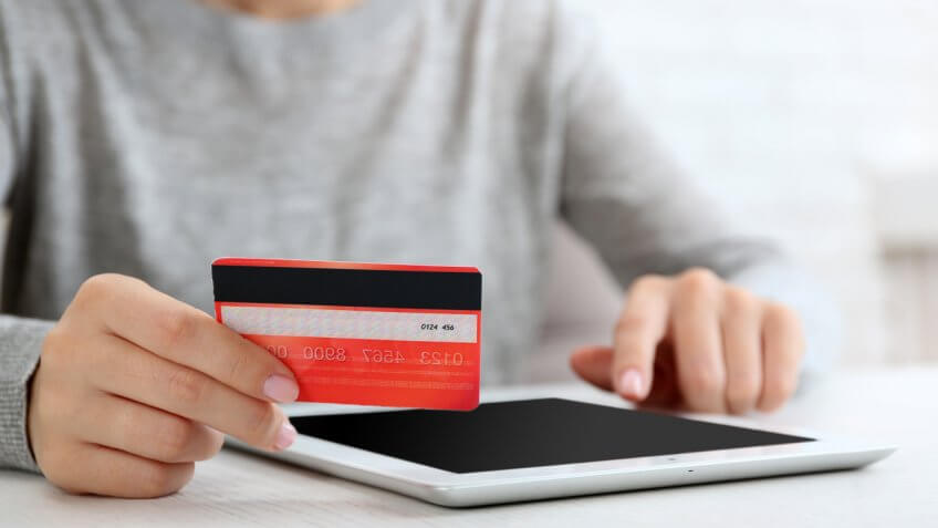 person holding credit card and smart tablet ipad