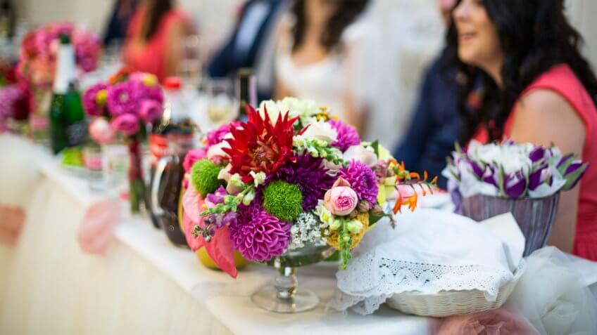 group of people sitting table with floral arrangements