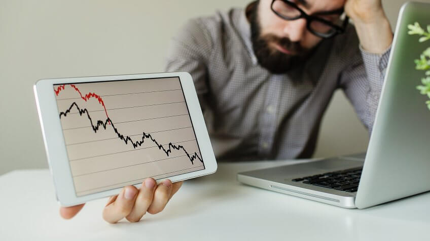 sad looking man holding ipad with chart of dropping stocks
