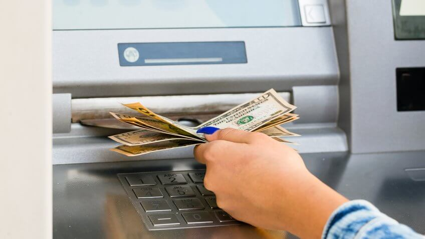 woman pulling $10 out of an ATM