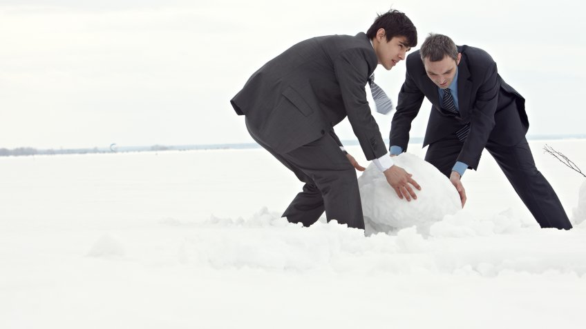 two men rolling a giant snowball