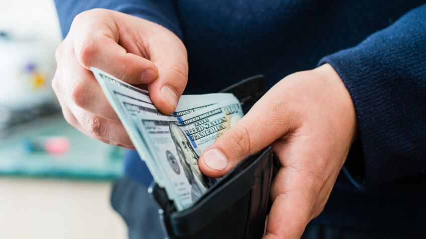 man pulling $100 cash money out of his wallet