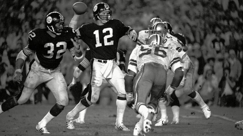 BRADSHAW HARRIS HENDERSON Pittsburgh Steelers quarterback Terry Bradshaw winds up to fire a pass during Super Bowl XIII against the Dallas Cowboys in Miami .