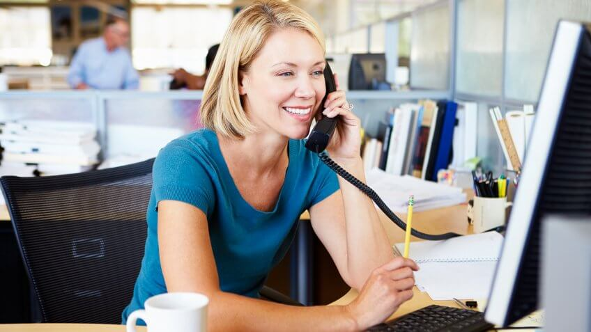 smiling woman on phone at work