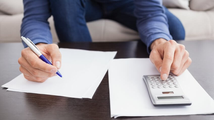 man writing on a paper whilst typing into a calculator