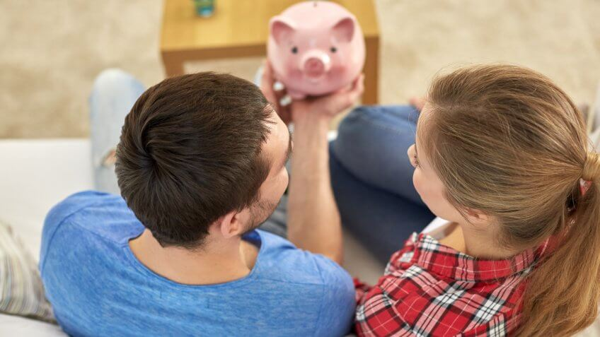 young couple holding a pink piggy bank