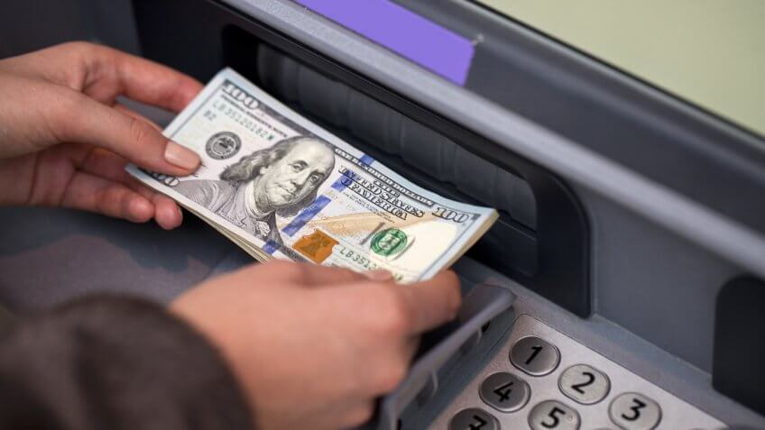 person holding $100 next to an atm