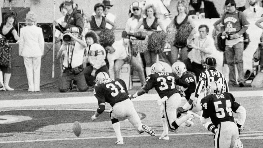 Los Angeles Raiders' Derrick Jensen (31), Lester Hayes (37) and Kenny Hill (48) chase a blocked punt into the end zone where they recovered it for a touchdown during first quarter action in super Bowl XVIII against the Washington Redskins, in Tampa Stadium.