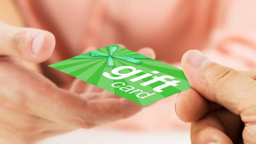 person passing another person a gift card