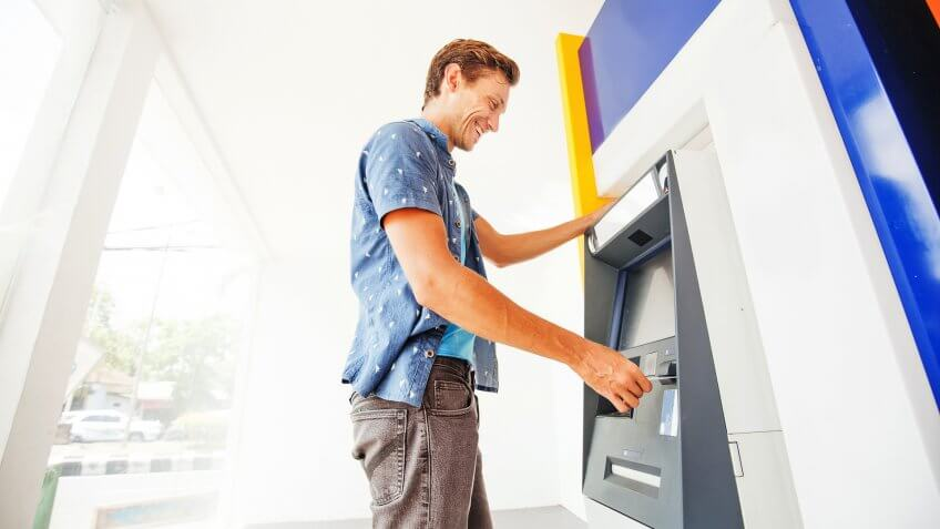 man happily using an ATM