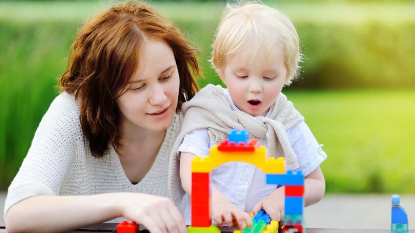 woman and child playing with legos