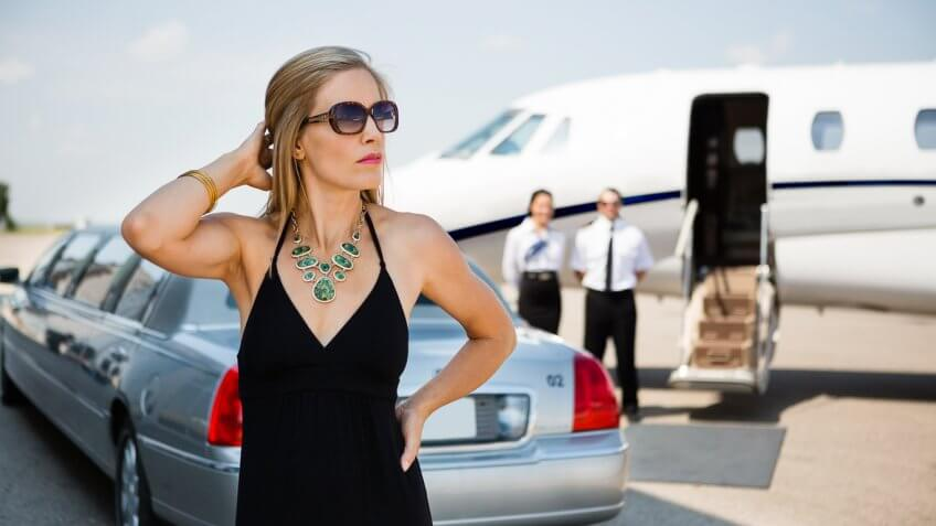 woman outside of a limo and private plane