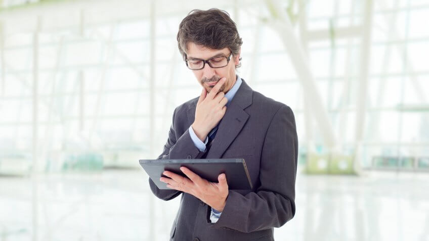 man looking inquisitively at his tablet