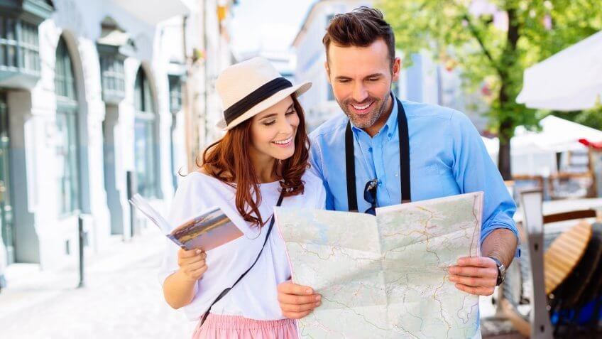 young couple traveling looking at map tourist