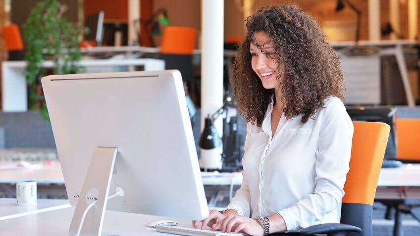 Woman happily typing on her computer