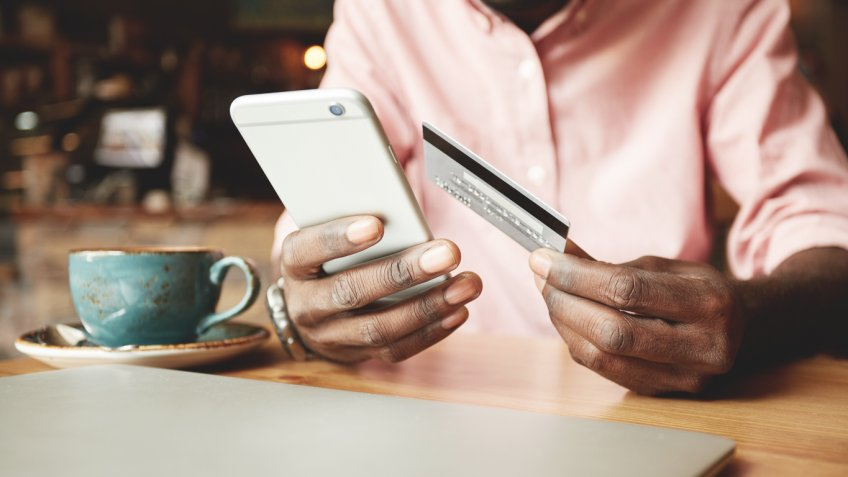 person holding credit card and iphone smart phone