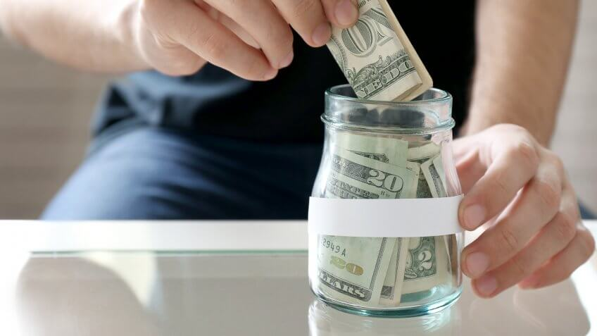 man putting dollar bill in a glass jar full of cash money
