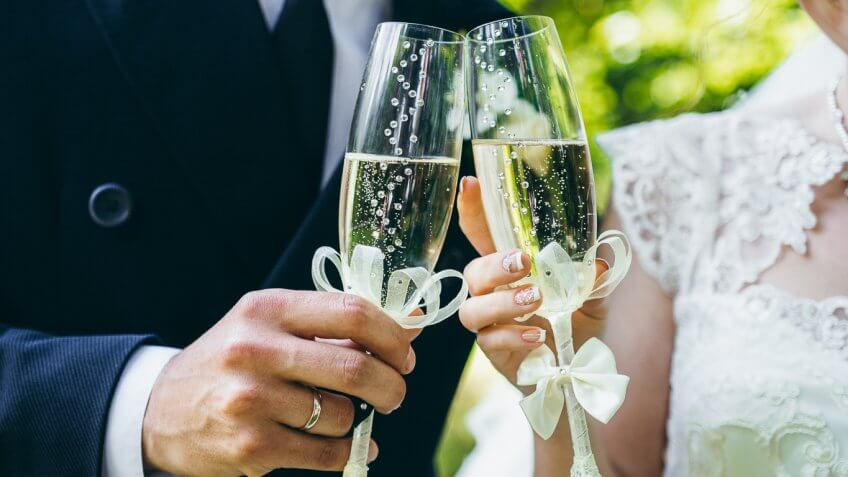 bride and groom clinking glass of champagne
