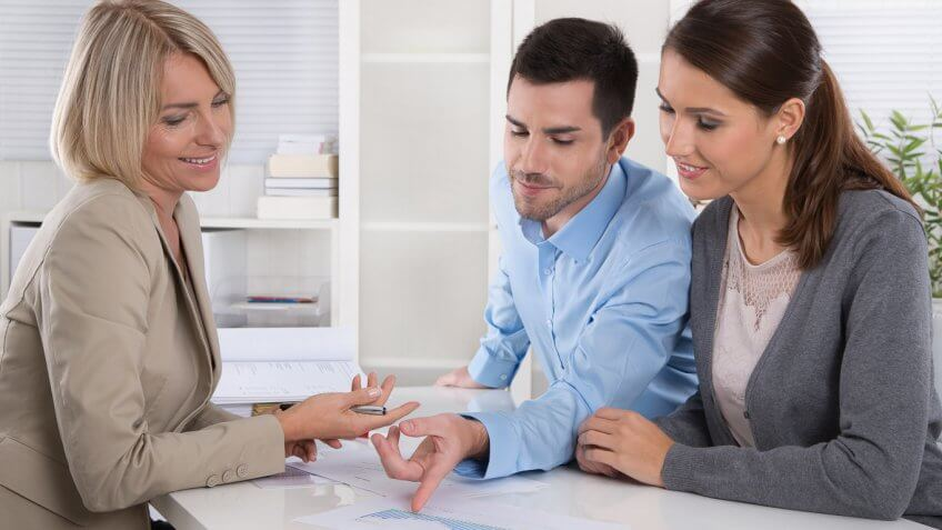 young man and woman reviewing documents with an adviser