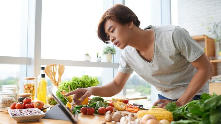 young man reading a recipe with ingredients laid out