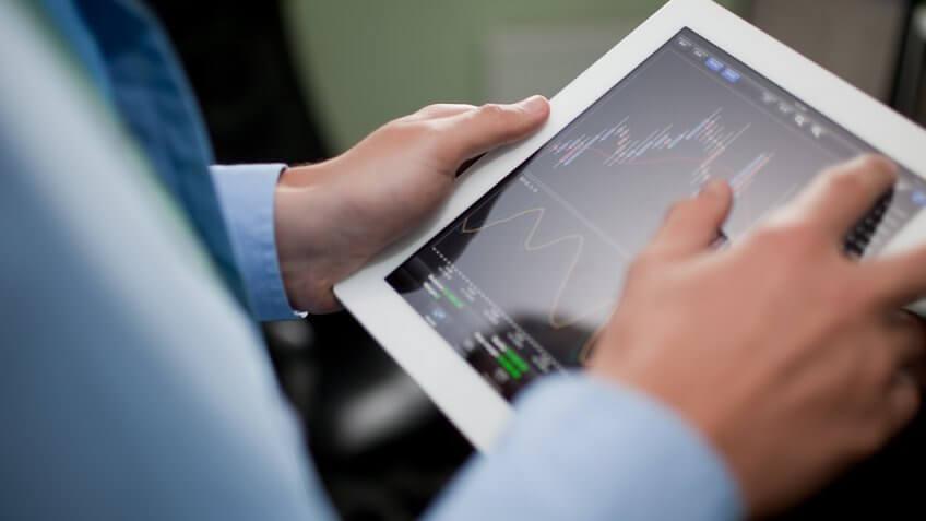 man looking at stocks on his ipad tablet