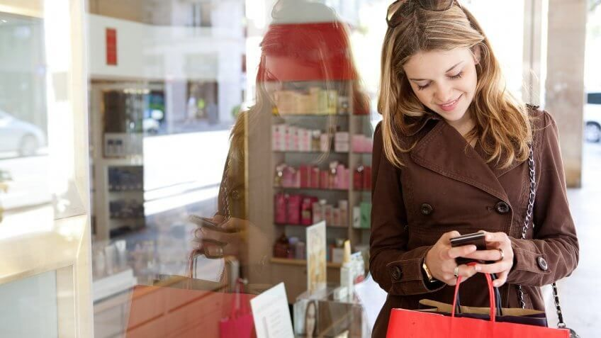 woman standing outside of a shop on her cell phone
