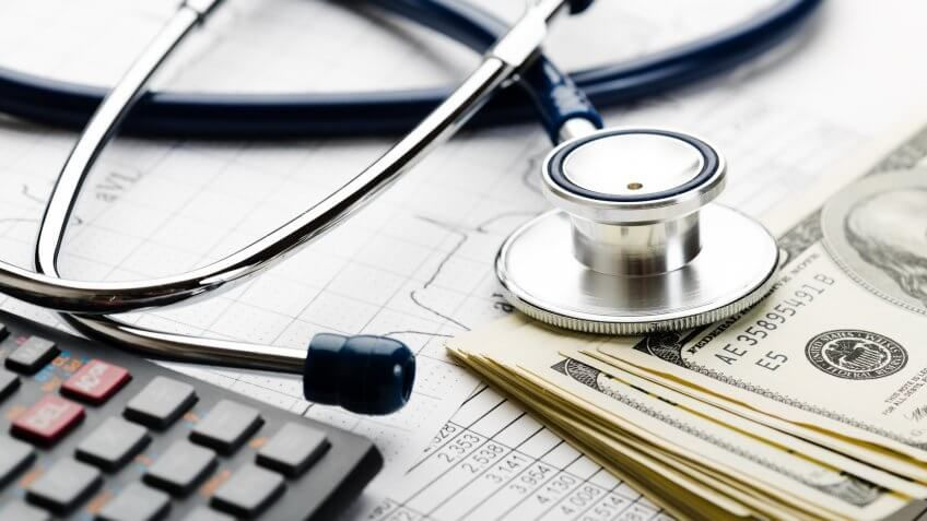 stethoscope over a calculator and pile of money